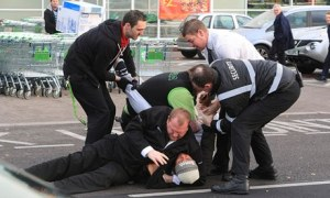 A shopper is restrained on the ground by security staff in the car park of an Asda store in Bristol